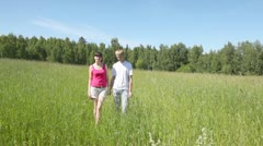 Guy with girl go across field holding hands and concerning grass Stock Footage