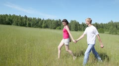 Guy with girl run across field parallel to wood Stock Footage