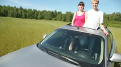 Guy with girl stand in aperture of roof of car. Stock Footage