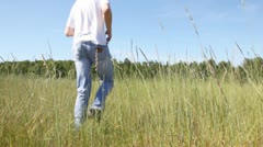 Guy blonde in jeans runs across field in grass to wood Stock Footage