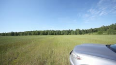 Jeep does two circles in field with grass before wood Stock Footage
