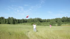 Girl holds rope from kite, and guy nearby looks in field Stock Footage