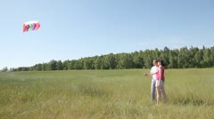 Guy and girl stand in field and have control over rope from kite Stock Footage