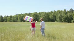 Guy and girl in field also try to start kite from earth Stock Footage