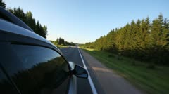 Car goes on asphalted highway among green woods Stock Footage