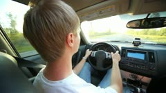 Nape of guy of blonde at wheel of car to road going Stock Footage