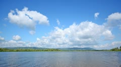 Clouds fly on blue sky over river in sunny weather Stock Footage