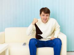 Guy sits on sofa and watches football on tv Stock Photos