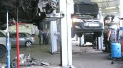Stock Video Footage of Mechanic elevate car on lifting-jack hoist in garage