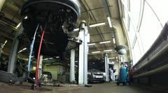 Stock Video Footage of Car mechanics elevate car on lifting-jack hoist in garage