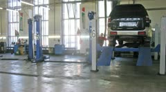Car lower from lifting-jack hoist in garage of service center Stock Footage
