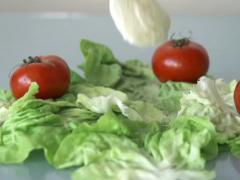 Mozzarella cheese falling on lettuce, slow motion shot at 480fps NTSC Stock Footage