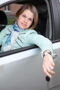 smiling caucasian woman sitting in land vehicle with car key - stock photo