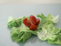 Tomato falling on lettuce leafs, slow motion shot at 480fps NTSC - stock footage