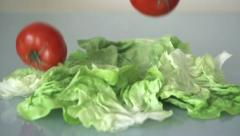 Tomatoes falling on lettuce leafs, slow motion shot at 480fps HD - stock footage