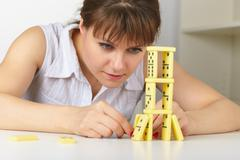 Stock Photo of young woman accurately builds tower of dominoes