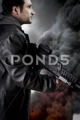 Stock photo of man with long leather jacket and assault rifle, black smoke background