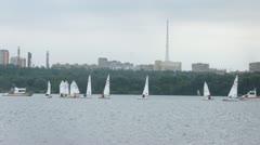 Yachts float down river against city landscape Stock Footage