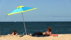 Couple under beach umbrella Stock Footage