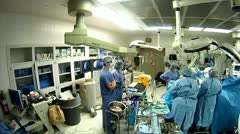 Panning shot with super wide angle lens of operating room during surgery - stock footage