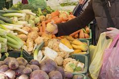 Picking organic vegetables on market - stock photo