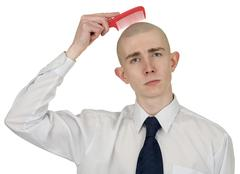 absolutely bald guy with a hairbrush - stock photo