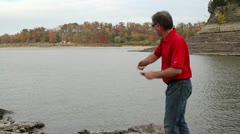 Man skipping 2 large rocks in Mississippi River Stock Footage