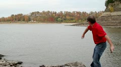 Middle aged man skipping a rock in the Mississippi River Stock Footage