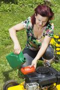 Mid age women adding oil to lawn mover Stock Photos