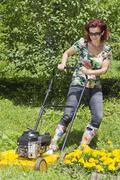 Smilling woman is mowing the grass-backwards - stock photo