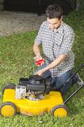 Man oiling  yellow lawn mover Stock Photos