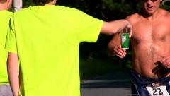Triathlon runners pass water station; 7 Stock Footage