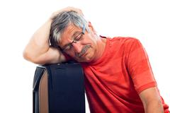 senior man sleeping on luggage - stock photo