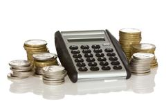 calculator and stack of coins - stock photo