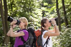 two women hiking in forest and looking with binoculars - stock photo