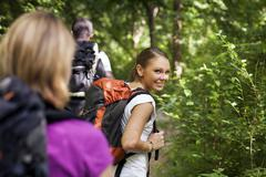 people with backpack doing trekking in wood - stock photo