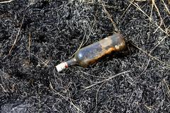 Empty liquor bottle in burn felt Stock Photos