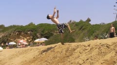 Freerunning stunt Cork (backflip 360 ) from a sand hill Stock Footage