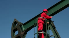 Worker in Action at Pump Jack Oil Well Stock Footage