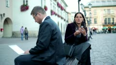 Business people sitting in the city with cellphone and laptop, steadycam shot - stock footage