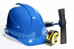 Hammer, tape line and blue hardhat Stock Photos
