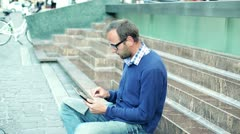 Young man with tablet computer sitting on the stairs, outdoors Stock Footage