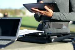 Liikemiehet kannettava tietokone, tabletti tietokone ja asiakirjat, ulkona Arkistovideo