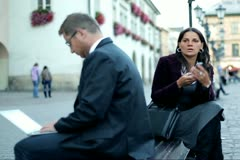 Business people sitting in the city with cellphone and laptop, steadycam shot Stock Footage