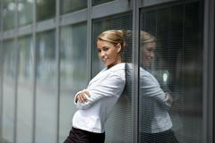 confident woman leaning on office building window - stock photo