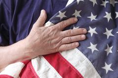 American flag with hand of a veteran.jpg - stock photo