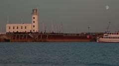 Scarborough lighthouse and tranquil sea with boat passing and moon in sky Stock Footage