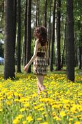 young brunette walking along the meadow - stock photo