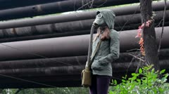 The girl in the gas mask promenade under the rain in the industrial zone Stock Footage