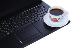 A cup of coffee on laptop keyboard Stock Photos